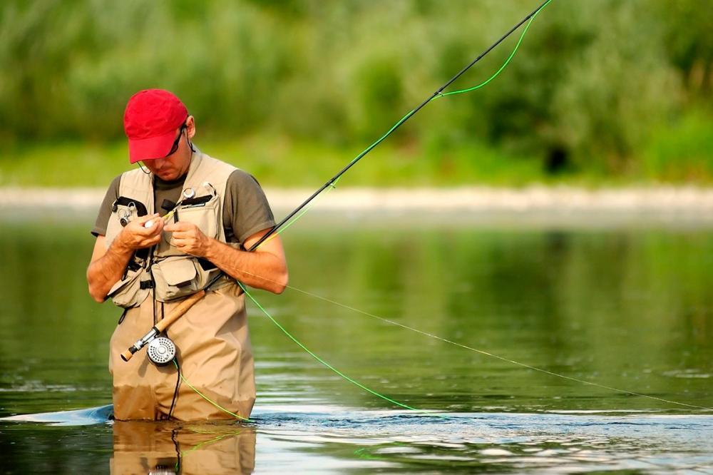 Нахлыстовик меняет мушку в реке