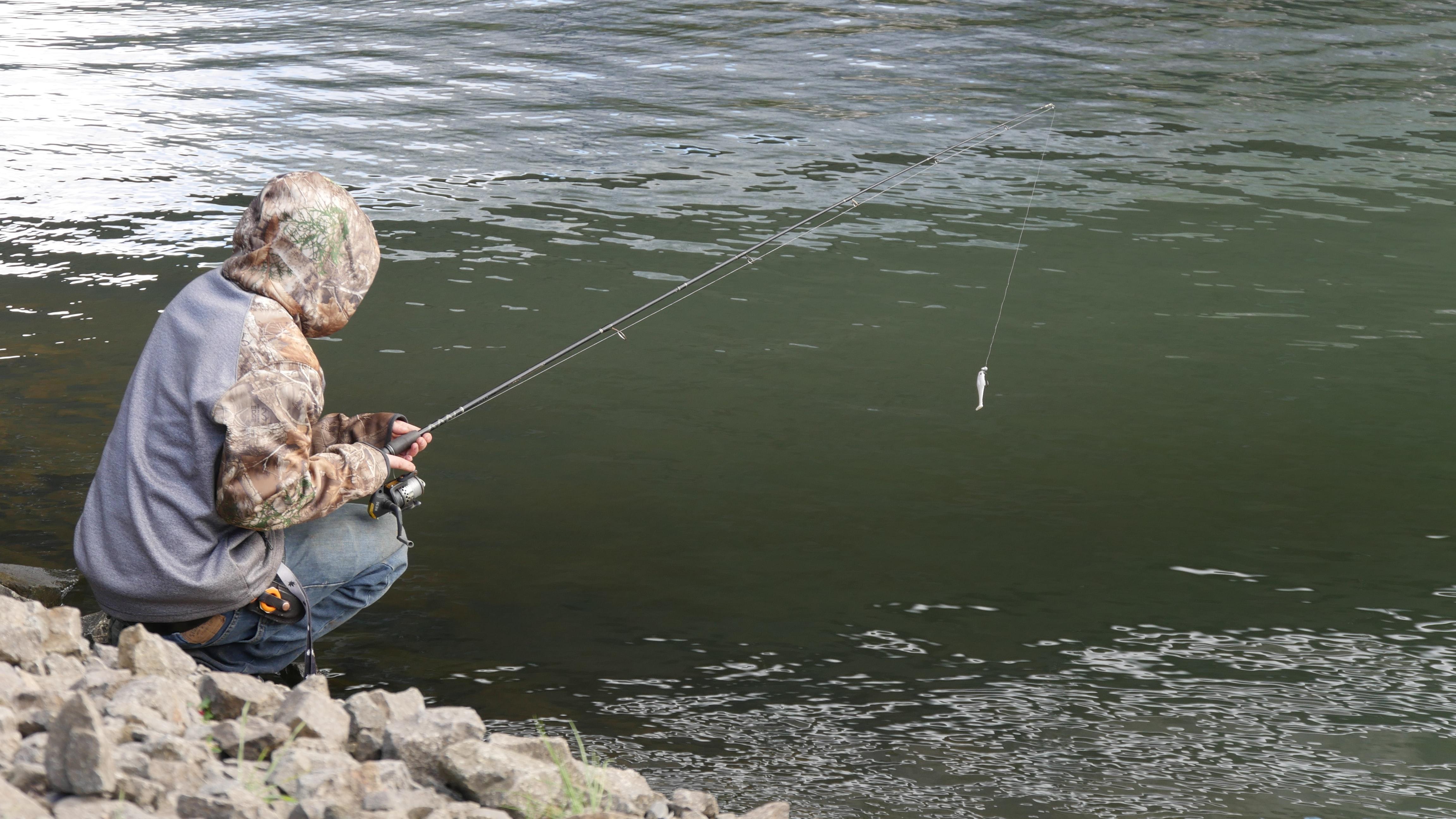 Рыбак на горной реке с блесной