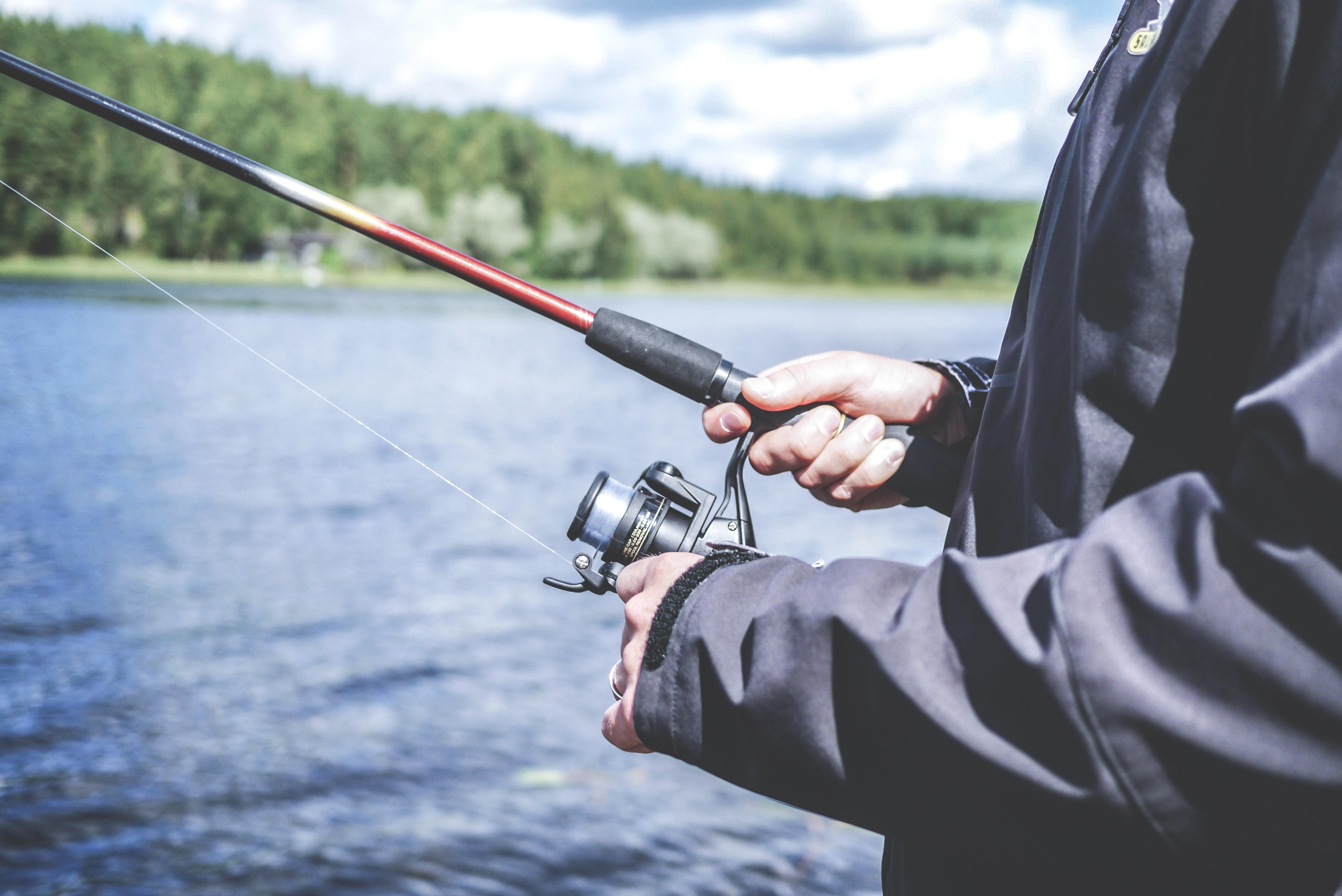 Рыболов у водоема со спиннингом
