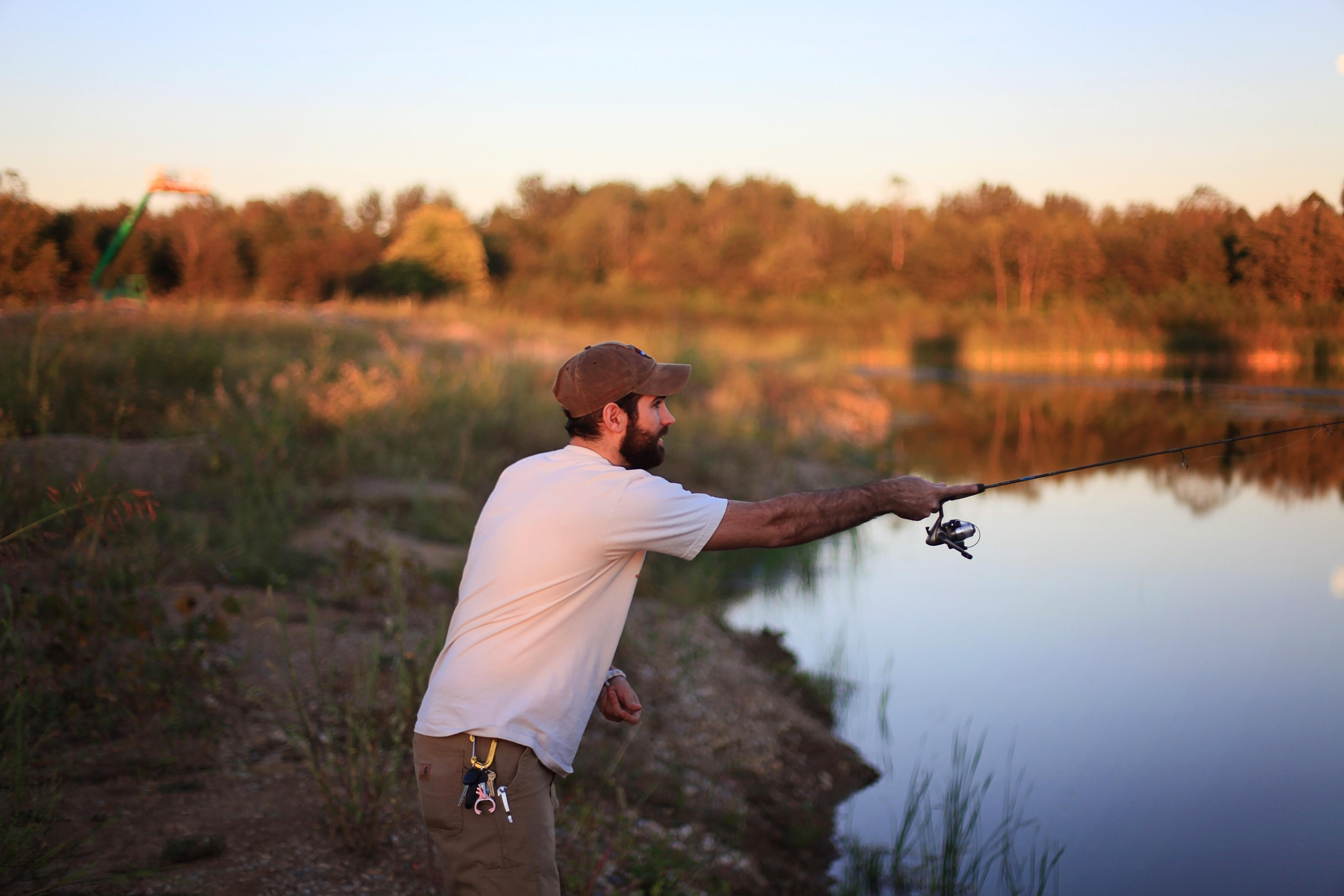 Рыбак забрасывает удочку осенью