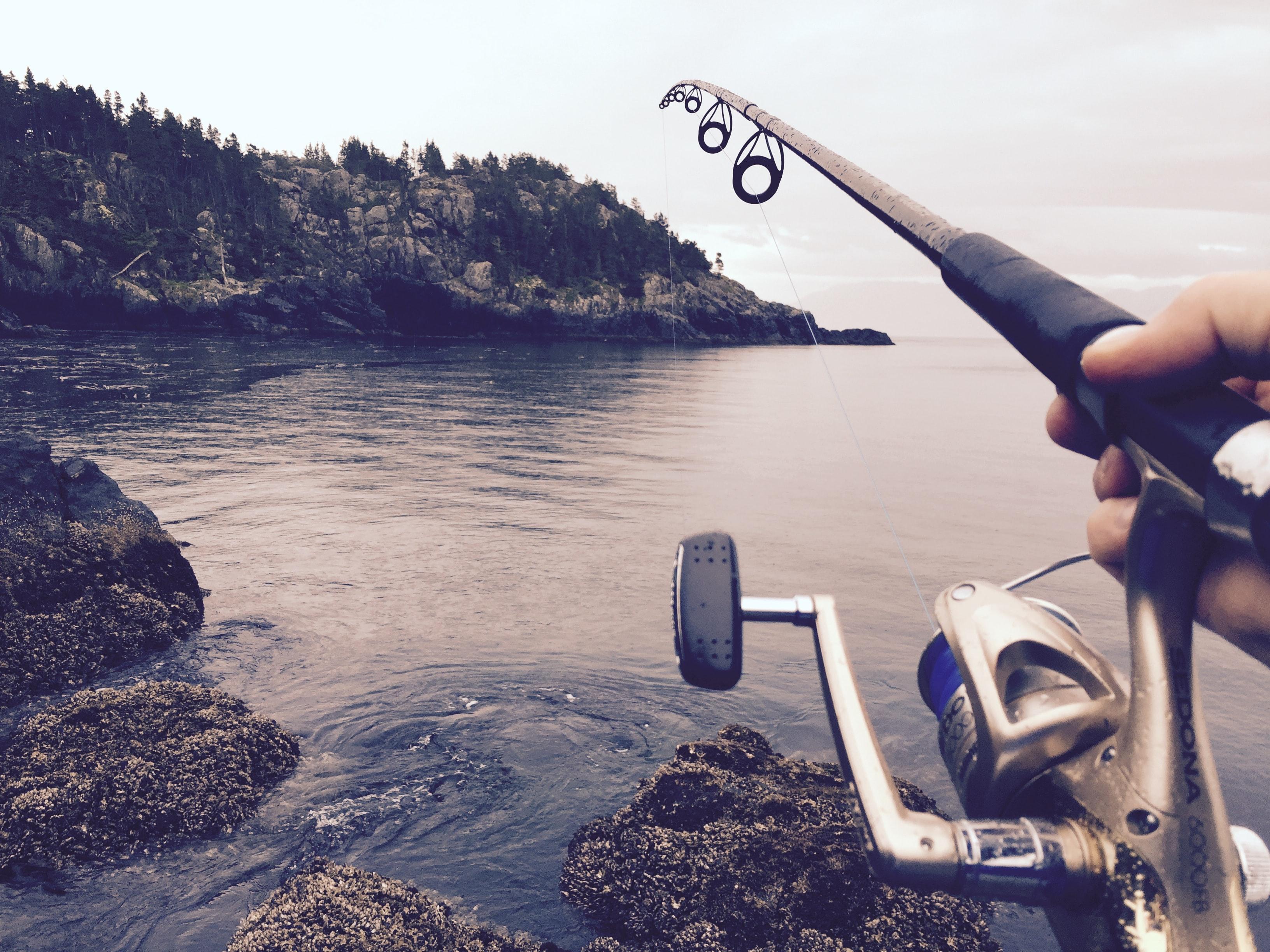Рыбак с удилищем в прекрасном водоеме
