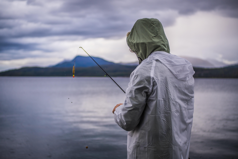 Рыболов в экипировке с поплавочной удочкой