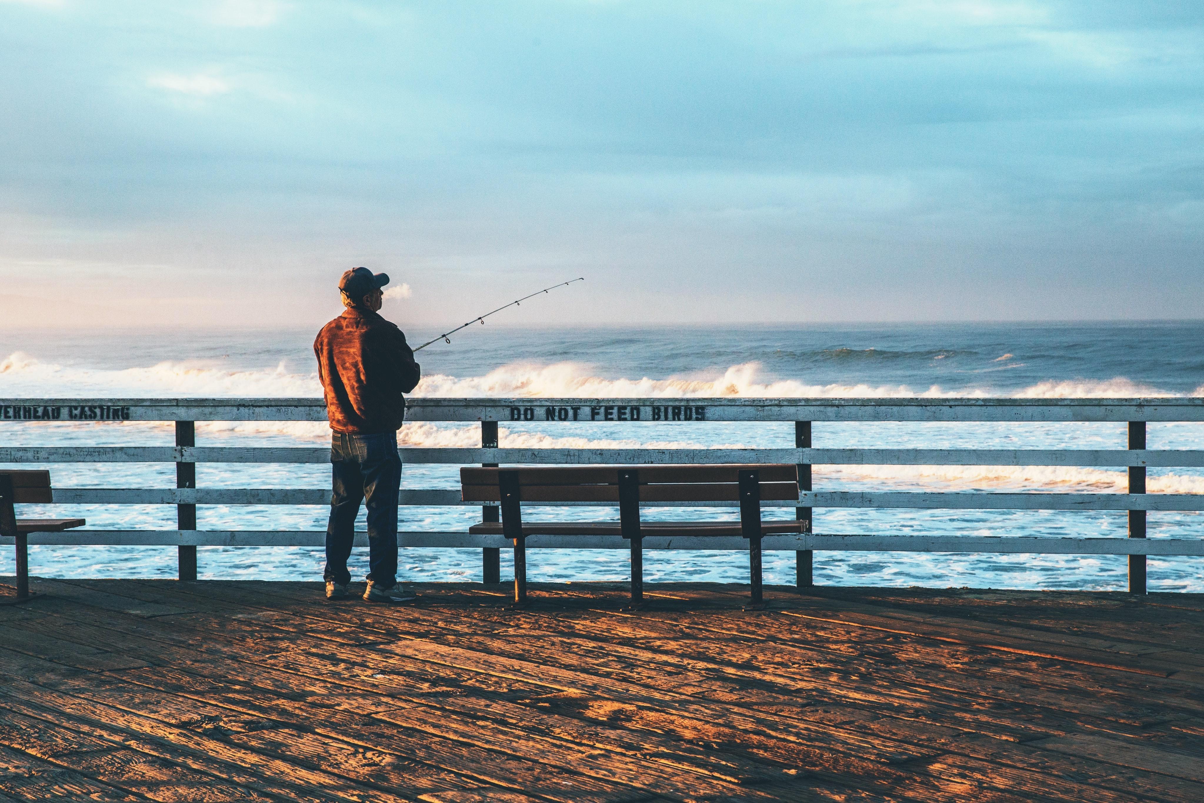 Рыболов за забором на фоне реки