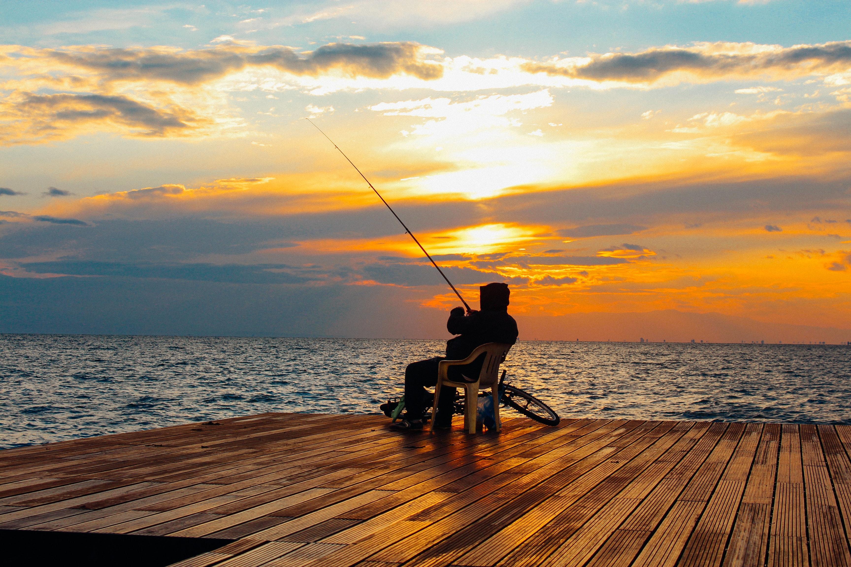 Рыбак на закате ловит на мостике