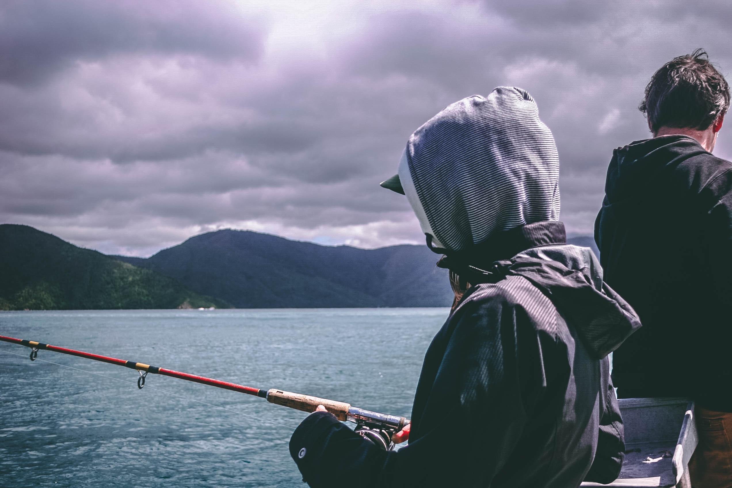 Рыболов в капюшоне ловит рыб