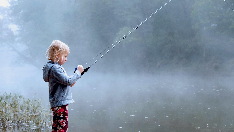 Маленький ребенок с удочкой на реке