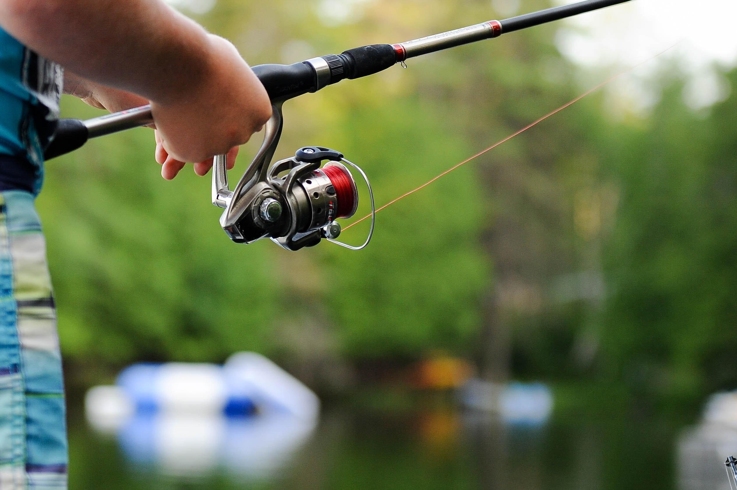 Рыбак крутит спиннинговую катушку при проводке