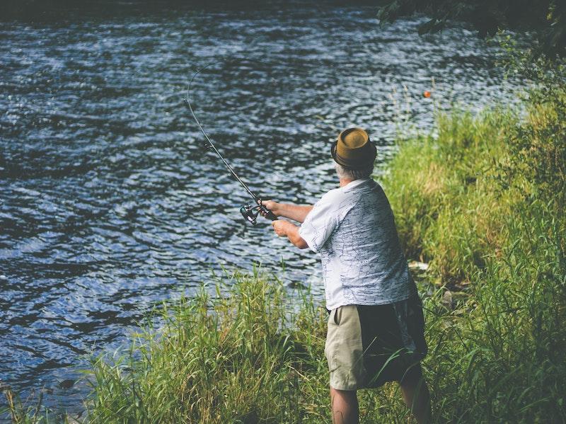 Рыбак забрасывает удилище в воду