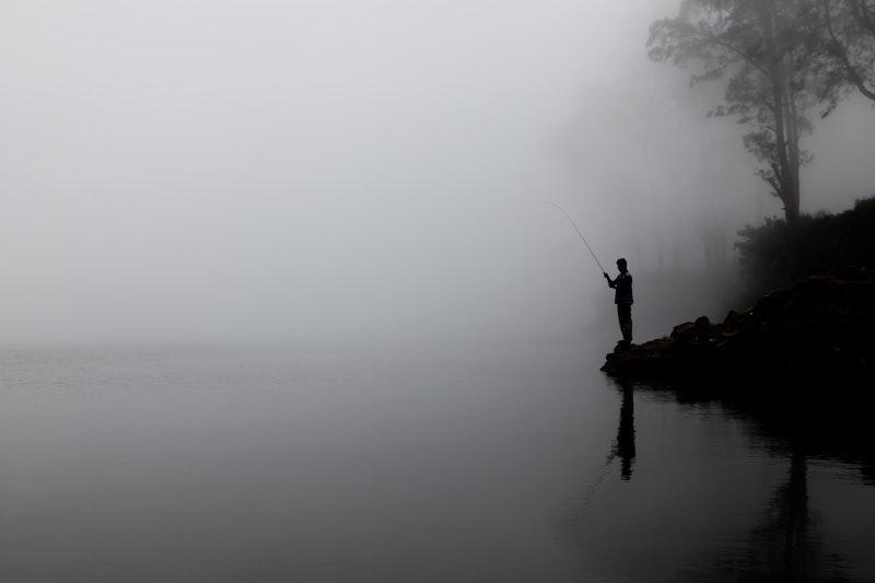 Рыбак на фоне реки в тумане