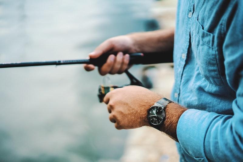 Рыболов крутит катушку на водоеме