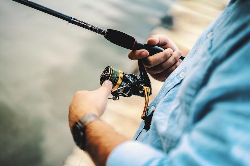 Рыболов открывает катушку для заброса