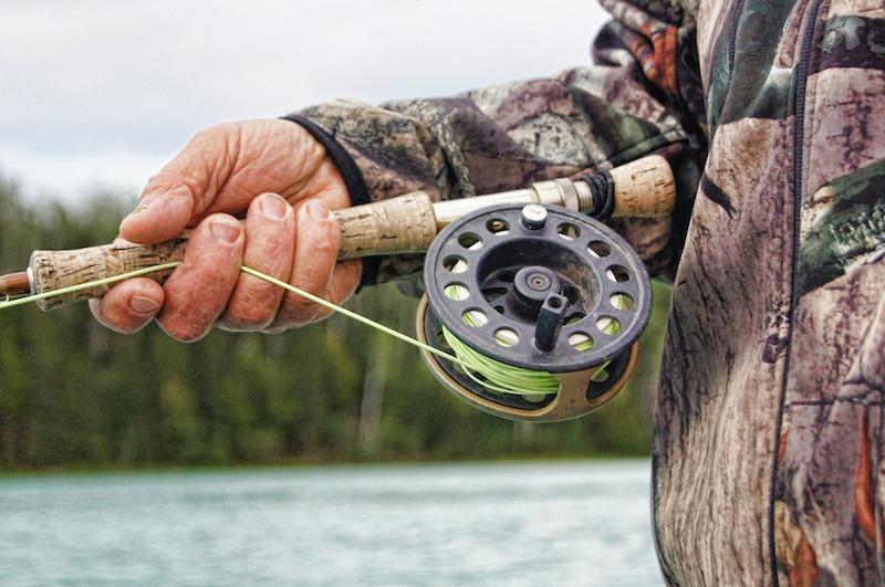 Нахлыстовая катушка в руках у рыболова