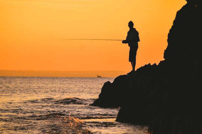 Рыбак с удилищем ловит рыбу с камней на закате