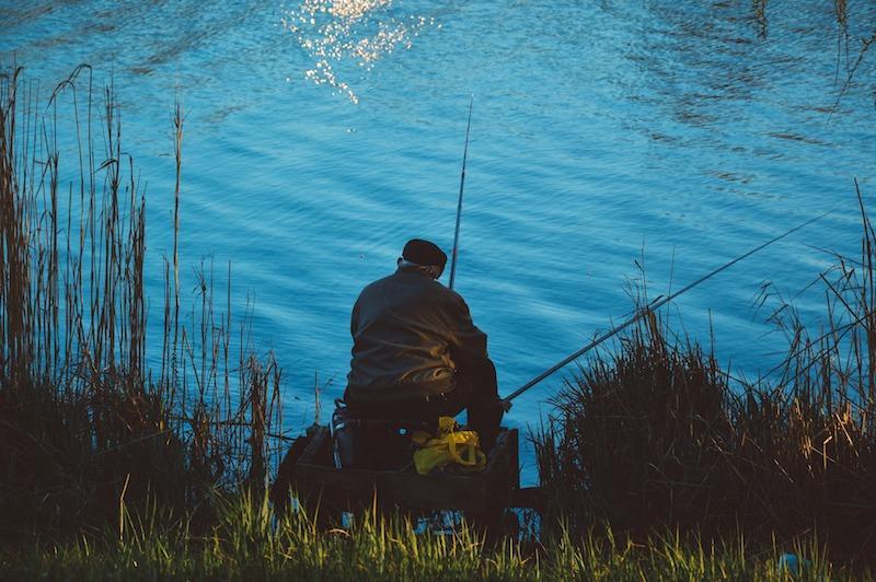 Рыболов с двумя удочками ожидает поклевку
