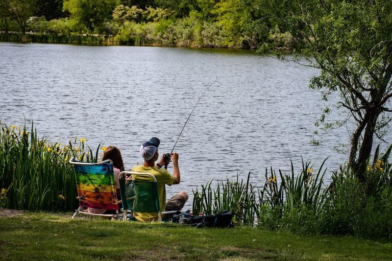 Рыболовы с удочками на платном водоеме