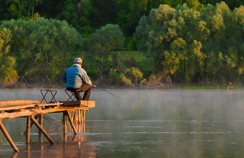 Рыбак на мостике с удочкой