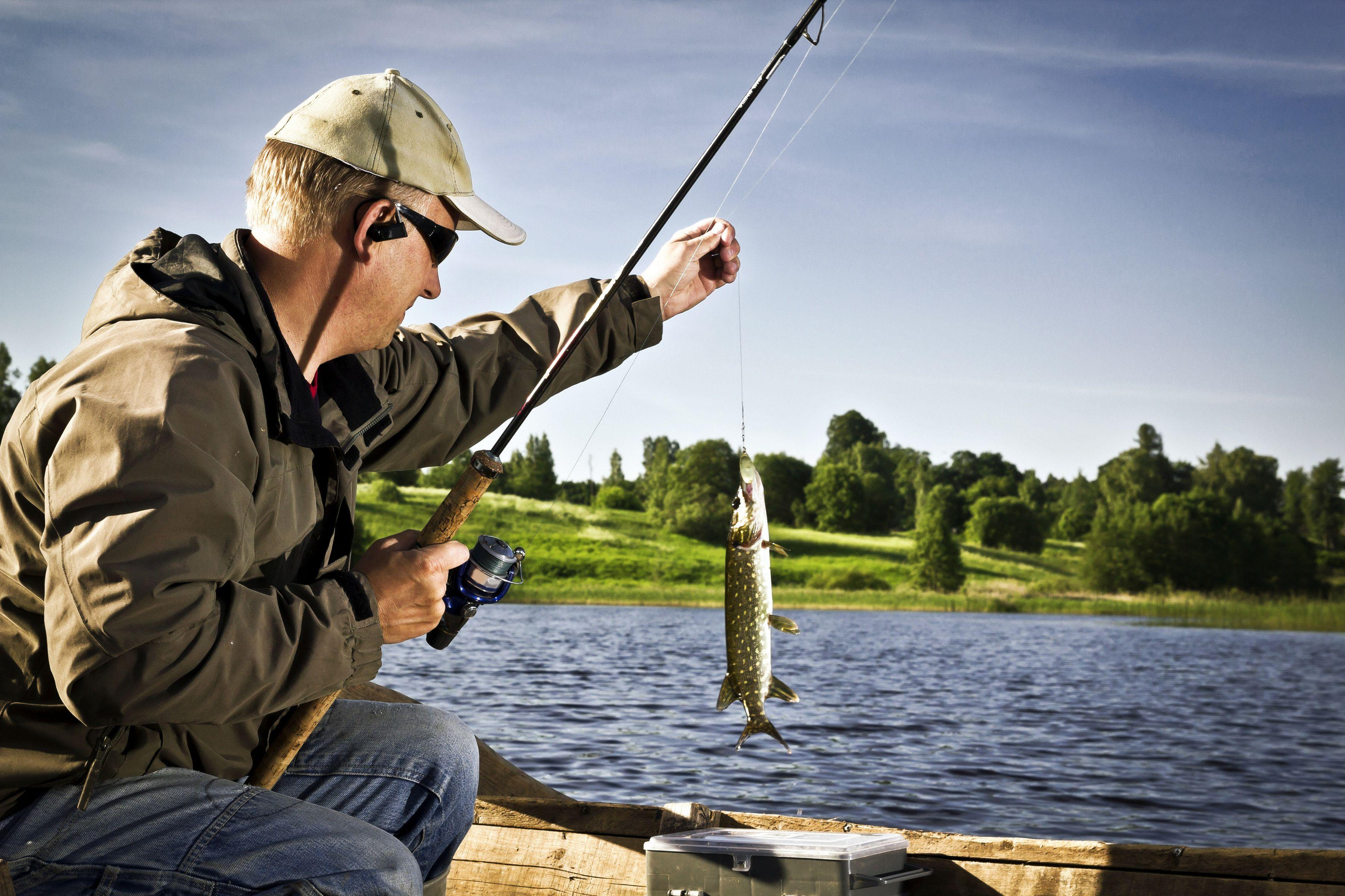 Рыболов со щукой с лодки