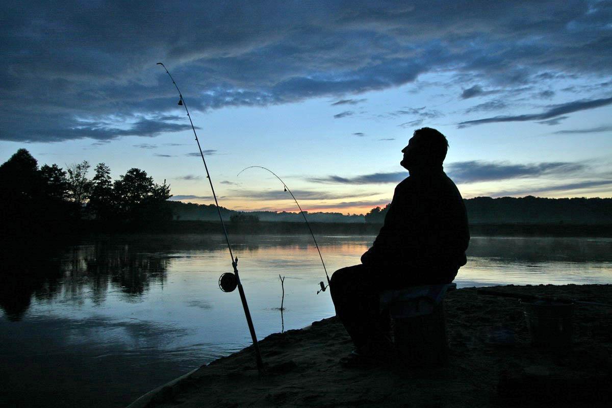 Рыбак с закидушками на закате
