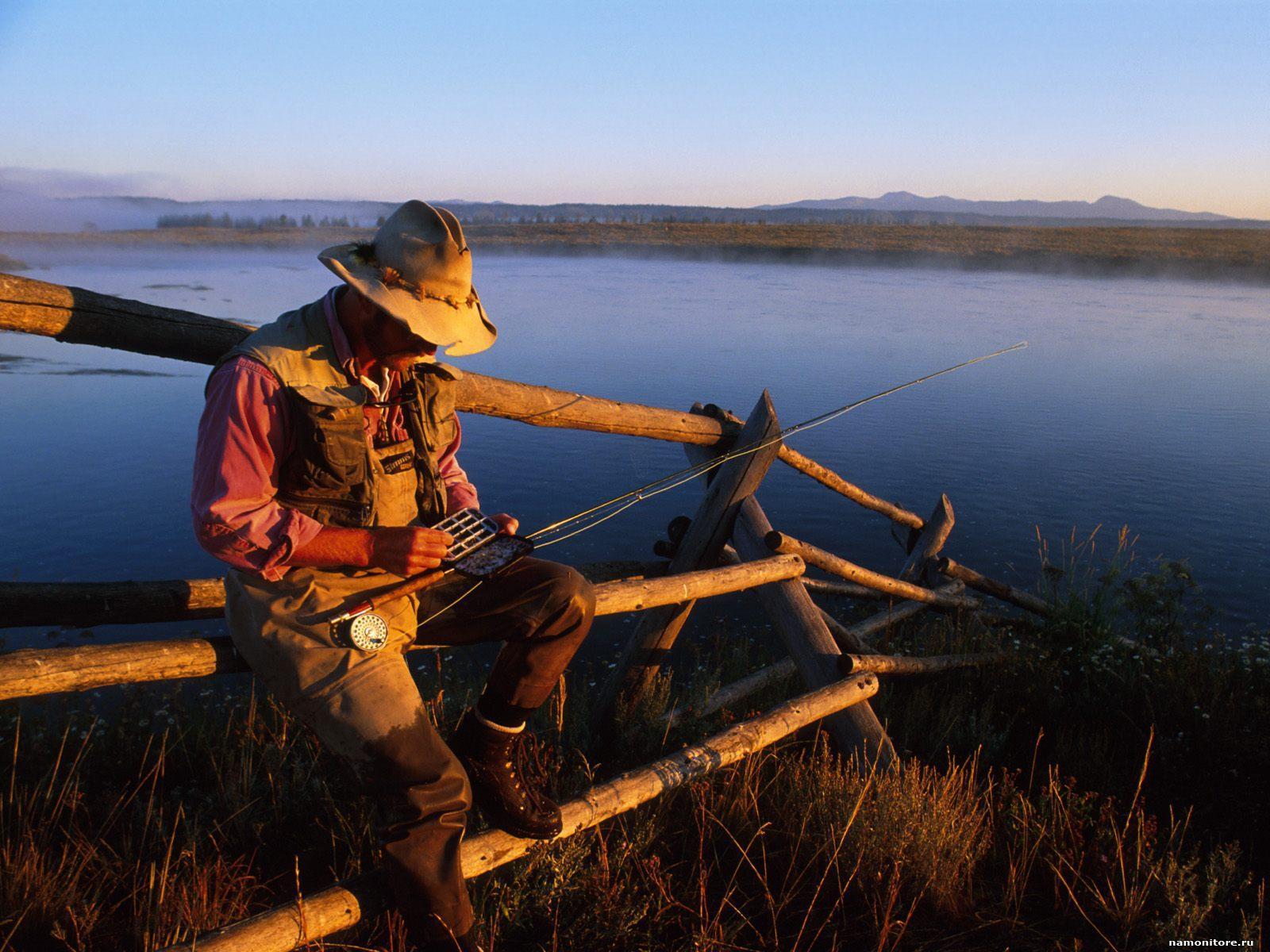 Рыболов со спиннингом на берегу реки