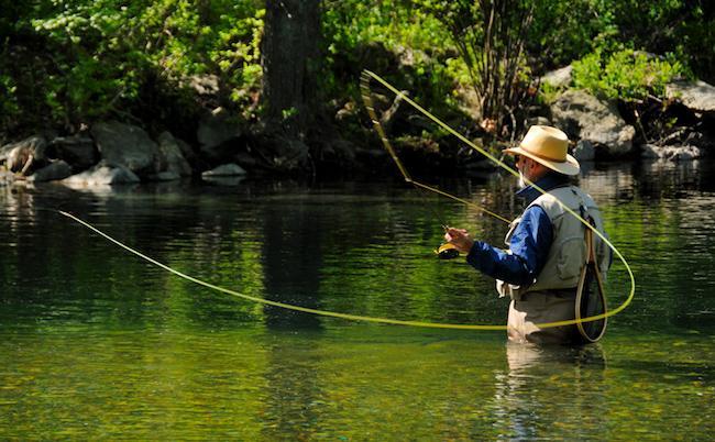 Рыбак ловит нахлыстом на реке